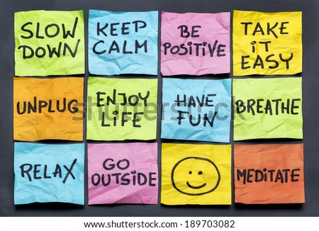 slow down, relax, take it easy, keep calm and other motivational  lifestyle reminders on colorful sticky notes - stock photo