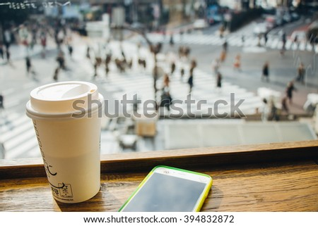 Slow life, Coffee time in rush hour of Big City with blur of people across pedestrian at Shibuya Junction, Tokyo, Japan - stock photo