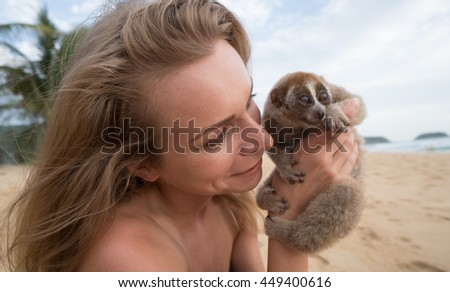 Slow loris in the hands of women on the beach. - stock photo