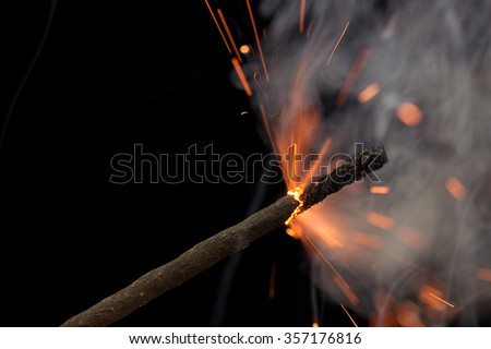 Slow-match is lit on a black background/Fuse burning  - stock photo