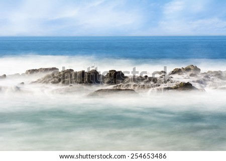 Slow motion scenic of a beautiful reef with seawater rushing over a rugged offshore reef in Laguna Beach, California.B - stock photo
