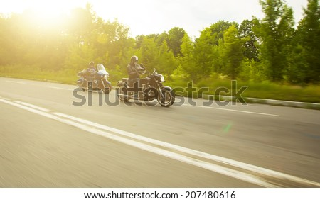 slow motion, two bikers riding unknown motorbike with blur movement, speed concept - stock photo