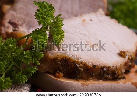 Slow roasted pork loin lying on wooden table - stock photo