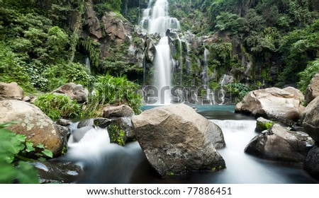 Slow shutter for moving water at Trois Bassin waterfall on Reunion Island - stock photo