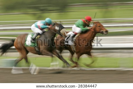 Slow shutter speed rendering of racing jockeys and thoroughbred horses.
