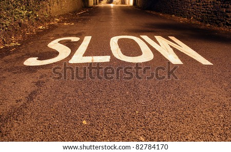 Slow sign painted on the road. - stock photo