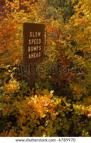 Slow speed bumps ahead sign with fall colors - stock photo