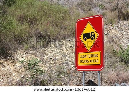 Slow turning Trucks Ahead sign 2 - stock photo