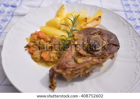 Slowly roasted spring lamb leg with rosemary and garlic served with sweet glazed onions, carrots, apples and baked potatoes on the simple rustic white plate. Fresh homemade dish for lunch or diner.