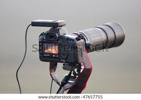 SLR camera on tripod with telephoto lens - stock photo