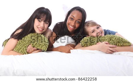 Slumber party for three teenage girl friends, a mixed race african american, oriental Japanese and blonde caucasian school mates in pyjamas lying on bed. - stock photo