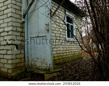 small abandoned house surrounded by leafless shrubs - stock photo
