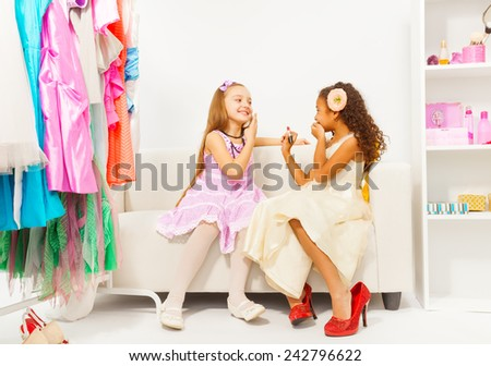 Small African girl puts make-up on her friend - stock photo