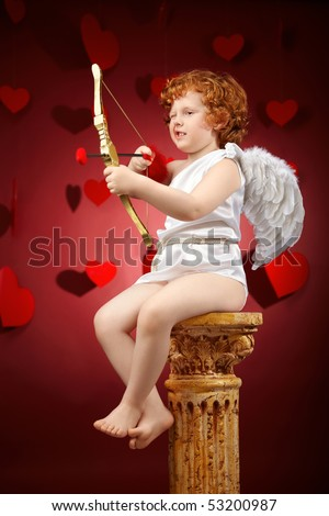 Small aiming boy in an image of the cupid on a red background - stock photo