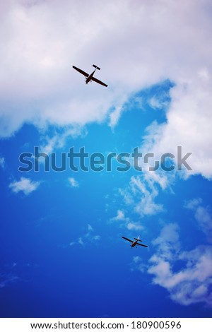 Small airplane in flight under a cloudy summer sky - stock photo