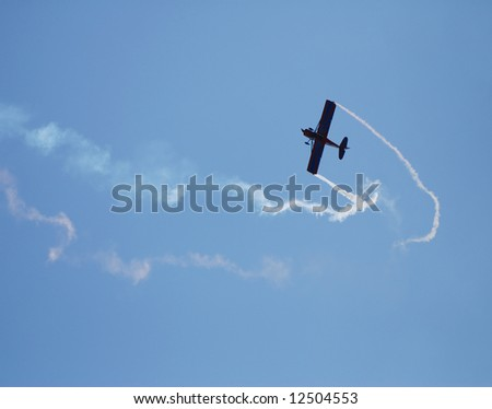 Small airplane performing aerobatic act - stock photo