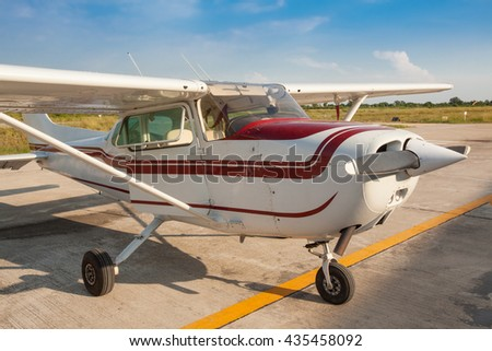 Small airplane with propeller in front parking on runway and preparing to fly. - stock photo
