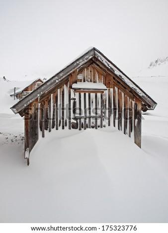 Small alpine cabin and snow drift - stock photo