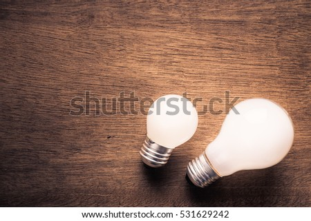 Small and big light bulb, small and medium sized business, coaching, training, or other comparison concept