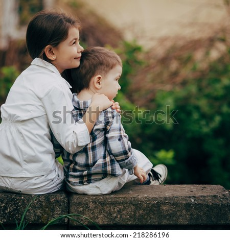 small and pretty children hugging and dreaming outdoor