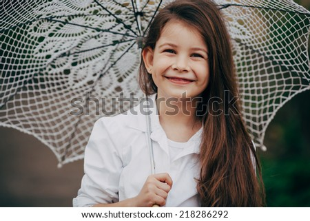 small and pretty  smiling girl with lace umbrella in white suit