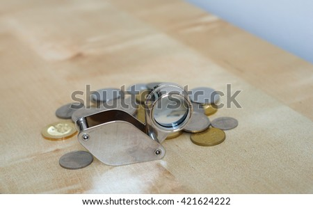 Small and unique magnifier with coins on wooden background - stock photo