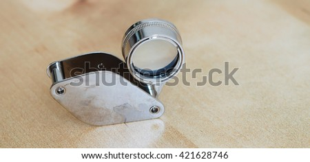 Small and unique shape of magnifier on wooden background - stock photo