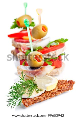 Small appetizer sandwiches isolated on white - stock photo