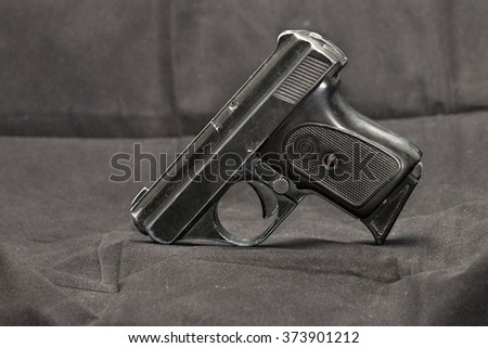 Small automatic pistol lying on dark background