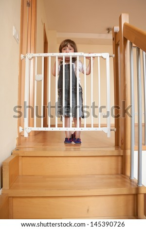 Small baby approaching safety gate of  stairs