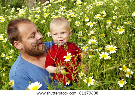 small baby boy and his father in the field of flowers on a summer day - stock photo