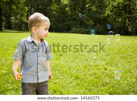 Small Baby Boy Looking On Soap Bubbles - stock photo