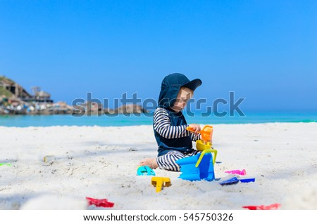 small baby boy toddler wearing sun protection swimwear sitting on white sandy beach with bright blue sky and ocean at background and playing with plastic sand toys
