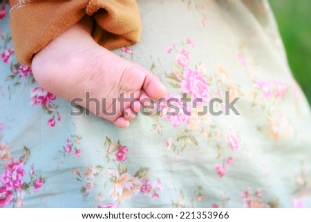 Small baby feet and carrying by mother - stock photo