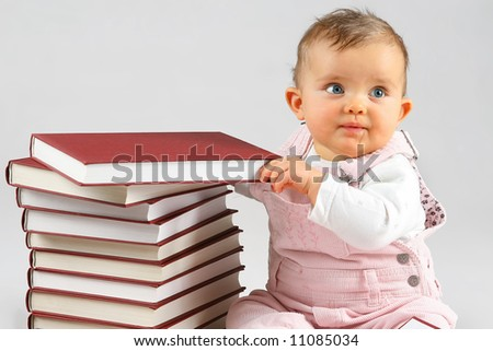 small baby girl and many red books with red cover - stock photo