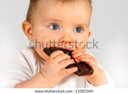 small baby girl holding big chocolate in hands - stock photo