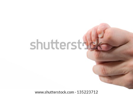 Small baby girl holding her father finger - stock photo