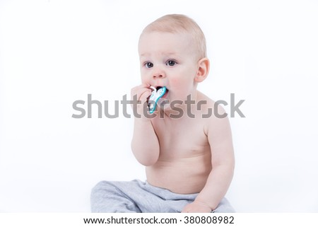 Small baby is licking and chewing his baby nipple - stock photo