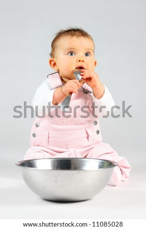 small baby is sitting with bowl and spoon - stock photo