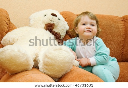 Small baby sitting in armchair with toy bear - stock photo