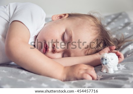 Small baby sleeping in his bed, dreaming. Nightime.  - stock photo