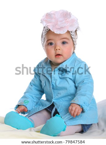 Small baby wearing a blue coat isolated on white - stock photo