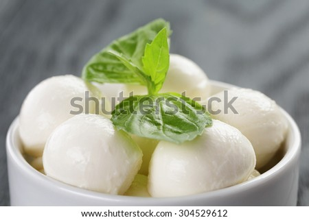 small balls of mozzarella in bowl with basil on wood table