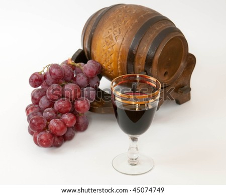 Small barrel, grapes and glass of vine on white