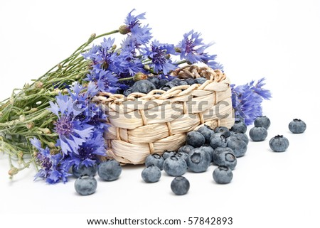 Small basket of ripe strawberries and bunch of cornflowers on white background - stock photo