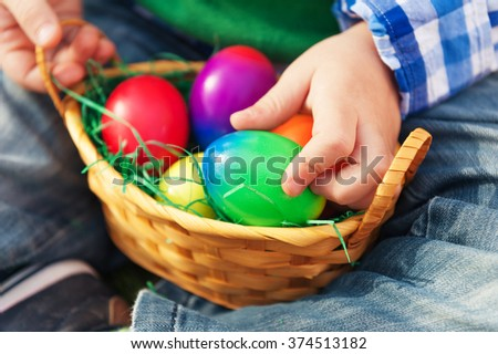Small basket with colorful easter eggs in baby's hands - stock photo