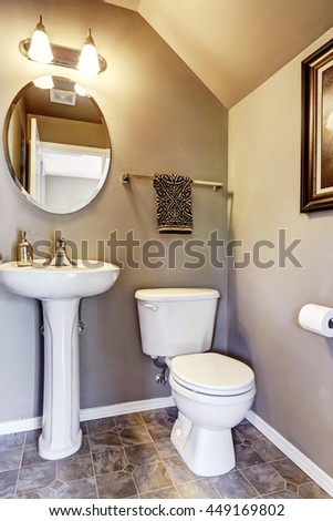 Small bathroom interior with tile floor and small mirror