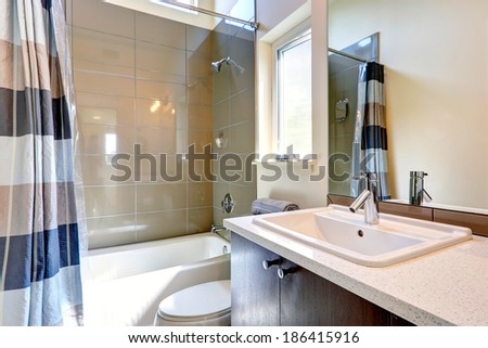 Small bathroom with window. View of washbasin cabinet with mirror and tub with tile wall trim - stock photo