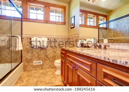 Small bathroom with wooden cabinet and glass door bath tub. - stock photo