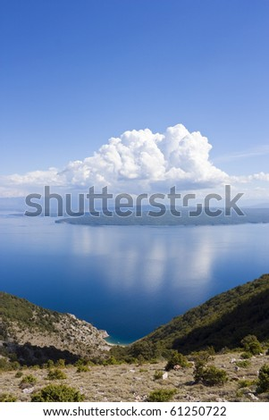 Small bay on croatia island cres, view to island krk with some clouds on blue sky - stock photo